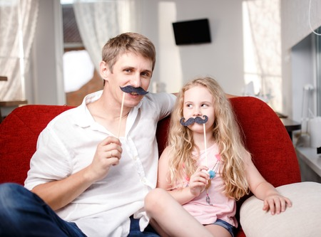Joyful father and daughter with artificial mustache while sitting togheter on red chair at home. Stock Photo