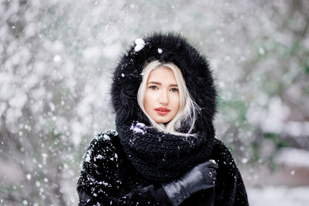 Portrait of beautiful blonde girl in a warm fur coat outdoor in a snowy forest.