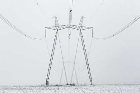 Hi-voltage electric power lines in a wintry foggy landscape, black and white photo.