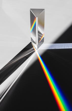 Un prisma che disperde la luce del sole che si divide in uno spettro su uno sfondo bianco.