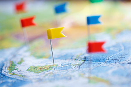 Macro photo with flag pushpins and world map.Travel concept