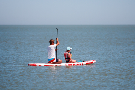 Father and daughter together paddling on a sup board