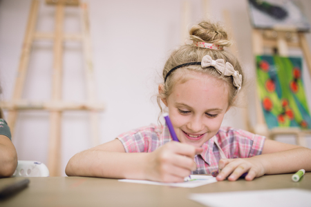Blonde cute smiling seven-year-old girl, draws at the table in the creative studio Stok Fotoğraf