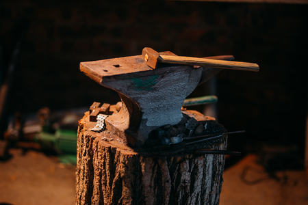 An old anvil attached to a wooden base stands in a private blacksmiths workshop.