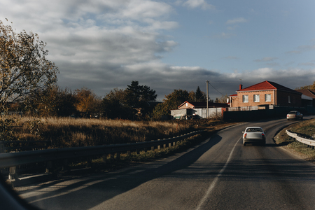 Asphalt road through the countryside. View from the car