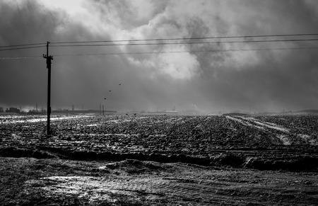 View of the frozen plowed field, the suns rays breaking through the dramatic clouds, industrial buildings can be seen in the distance. Black and white photo 写真素材