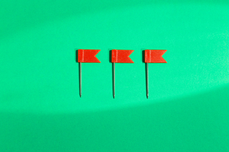 Three red little flag pins on a green background. View from above Imagens