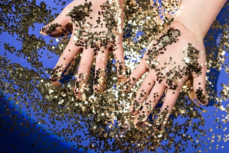 Hands of a child in gold glittering confetti on a blue background, top view. Birthday and holiday Banco de Imagens