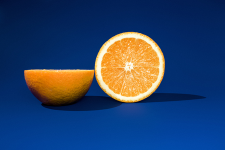 Two halves of ripe orange on a blue background in bright sunlight