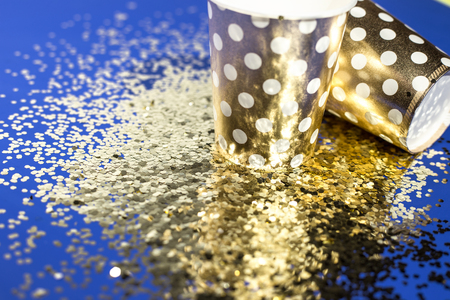 Golden paper cups for birthday party with golden confetti on blue background