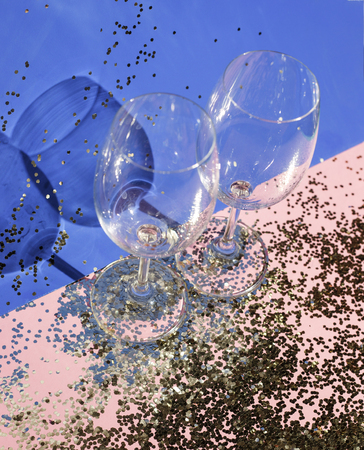 Empty glass goblets for champagne in golden confetti on the table. Festive background. Party concept