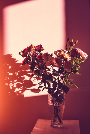 A bouquet of roses in a glass vase stand on a wooden stool against the background of the wall in the rays of sunlight