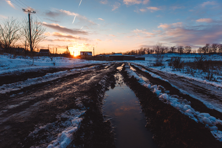 Country dirt road with muddy puddles and melting snow in early spring at sunset