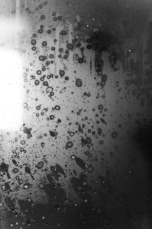 Closeup of condensation patterns on glass window, water droplets with light reflection and refraction, black and white abstract background Banco de Imagens