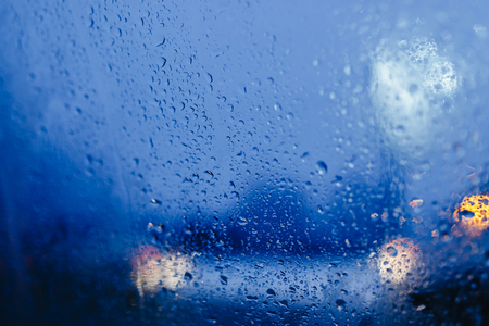 Night city lights through windshield abstract background water drop on the glass lights and rain Banco de Imagens