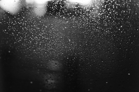 Closeup of condensation patterns on glass window, water droplets with light reflection and refraction, black and white abstract background Stock Photo