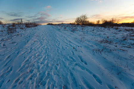 Snowy pathway countryside at sunset