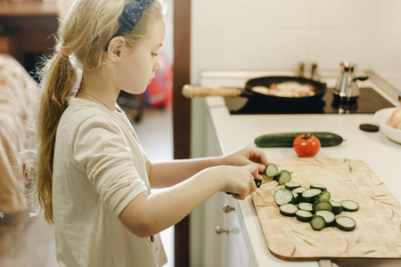 Little blonde girl cutting vegetables while cooking in kitchen at home