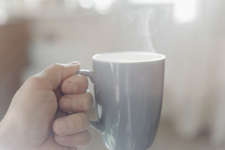 Man hand holding a cup of hot black coffee or americano with blurred natural background and morning sunlight
