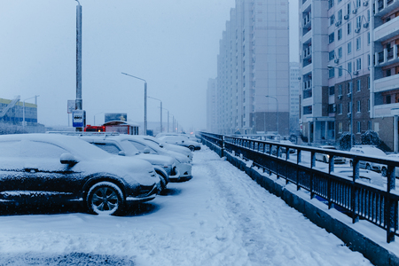 Winter snow city street scene. Snow covered cars on winter street in Russia