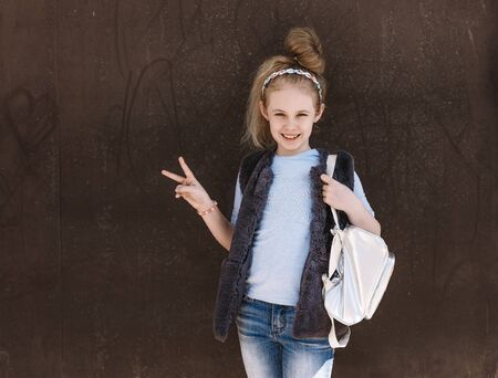 Charming eight-year-old girl in a trendy outfit with a backpack standing on the street on a sunny day Reklamní fotografie