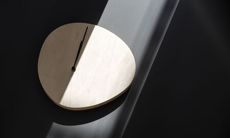 Wooden wall clock hanging on a gray wall in a beam of sunlight