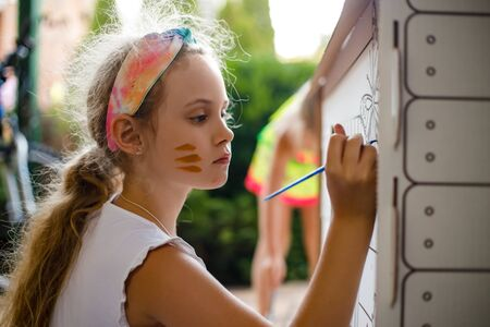 Girl paints a cardboard house at summer day, outdoor Reklamní fotografie