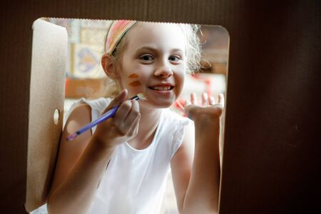 Happy girl paints on her face looking thru window of cardboard house Reklamní fotografie