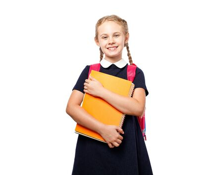 Cheerful 8 years old schoolgirl with backpack wearing uniform standing isolated over white background. Ready for school Reklamní fotografie