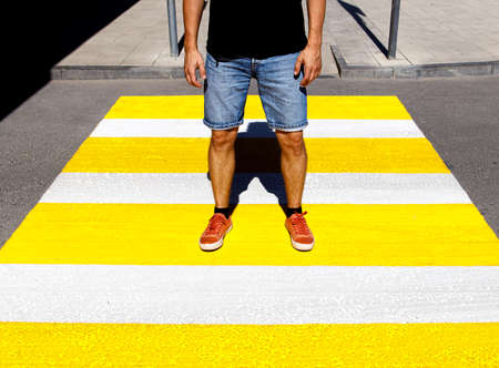 A young man in a black T-shirt and denim shorts stands at a pedestrian crossing.
