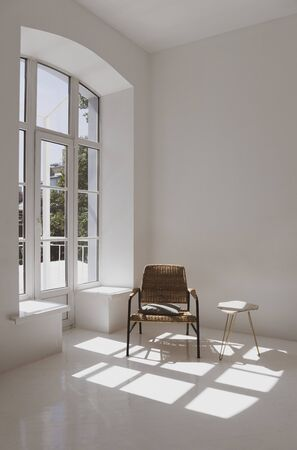 Empty white sunny room with wicker chair and table. Minimalist design. Reklamní fotografie