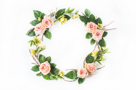 round frame wreath with pink roses, yellow flowers, branches, leaves and petals isolated on white background. flat lay, overhead view Stockfoto