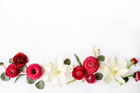 Pink and red roses or ranunculus, white tulips and green leaves on white background. Flat lay, top view