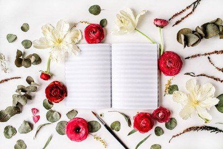 Workspace. Notebook or sketchbook, pink and red roses or ranunculus, white tulips and green leaves on white background. Flat lay, top view