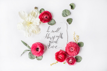 """Uitdrukking """"Doe kleine dingen met grote liefde"""" geschreven in kalligrafie stijl op papier met roze, rode rozen, ranonkel, witte tulpen en groene bladeren op een witte achtergrond. Plat, bovenaanzicht"""