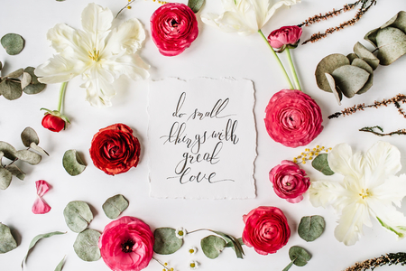 Phrase Do small things with great love written in calligraphy style on paper with pink, red roses, ranunculus,   white flowers and green leaves isolated on white background. Flat lay, top view
