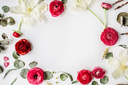 wreath frame with pink and red roses or ranunculus, white tulips and green leaves on white background. Flat lay, top view
