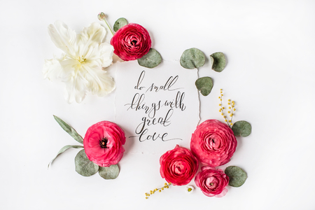 Phrase Do small things with great love written in calligraphy style on paper with pink, red roses, ranunculus,   white tulip and green leaves isolated on white background. Flat lay, top view Reklamní fotografie