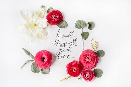 """Uitdrukking """"Doe kleine dingen met grote liefde"""" geschreven in kalligrafiestijl op papier met roze, rode rozen, ranunculus, witte tulp en groene bladeren geïsoleerd op een witte achtergrond. Plat leggen, bovenaanzicht"""