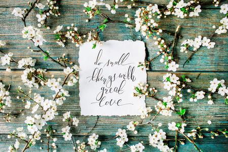 """Uitdrukking """"Doe kleine dingen met grote liefde"""" geschreven in kalligrafie stijl op papier met krans frame met witte bloemen en takken op een oude retro houten munt tafel achtergrond. plat, bovenaanzicht, bovenaanzicht Stockfoto"""