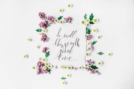 wedding table decor: Phrase Do small things with great love written in calligraphy style on paper with wreath frame with lilac and chamomile isolated on white background. flat lay, overhead view, top view Stock Photo