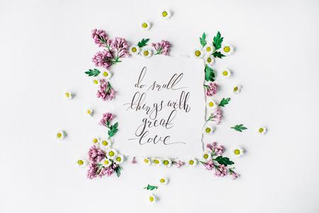 """Uitdrukking """"Doe kleine dingen met grote liefde"""" geschreven in kalligrafie stijl op papier met krans frame met lila en kamille op een witte achtergrond. plat, bovenaanzicht, bovenaanzicht Stockfoto"""