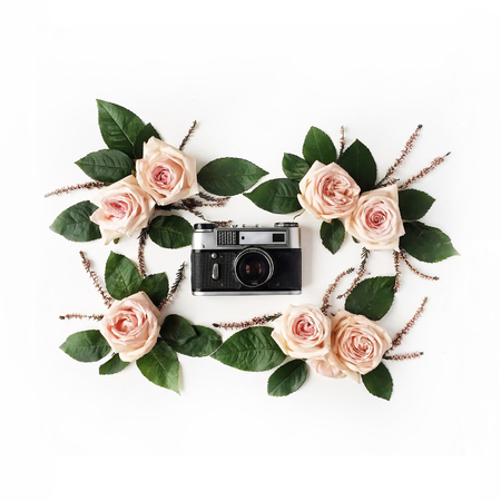 Flat lay. Vintage retro photo camera, beige roses and green leaves, top view