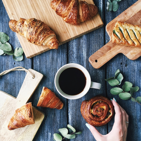 sweet pastries: Breakfast with croissants, leaves, cutting board and black coffee composition with girl hand on wooden retro background. Flat lay, top view