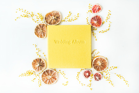 wedding photo album: yellow wedding photo album and frame with dry oranges and branches of mimosa isolated on white background. flat lay, overhead view