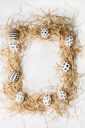 stars and stripes: Easter eggs in the nest painted in monochrome style isolated on white. Flat lay. Drops, flowers, hearts, stars, stripes Stock Photo