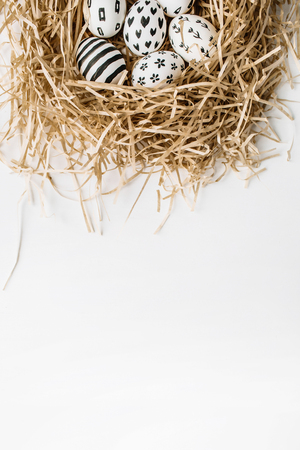 Easter eggs in the nest painted in monochrome style isolated on white. Flat lay. Drops, flowers, hearts, stars, stripes