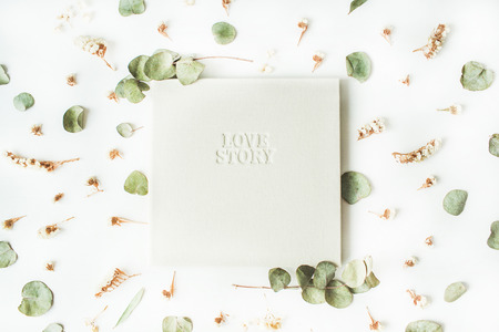 photo story: white wedding or family photo album with words love story, dry and fresh branches isolated on white background. flat lay, overhead view