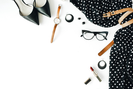flat lay feminini clothes and accessories collage with black dress, glasses, high heel shoes, purse, watch, mascara, lipstick, earrings on white background. Zdjęcie Seryjne