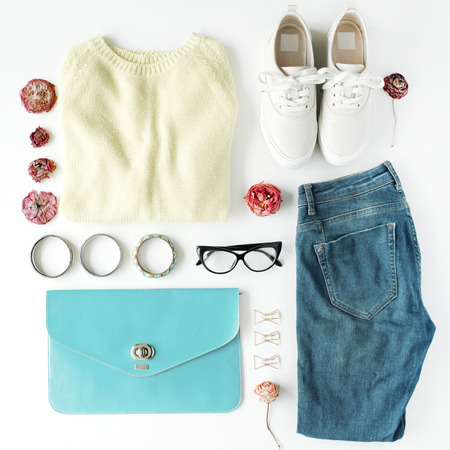 flat lay feminini clothes and accessories collage with cardigan, jeans, glasses, bracelet, clutch, shoes and dry roses on white background. Stock Photo